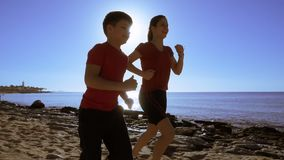 Silhouette of two kids running at morning exersises. Silhouette of two kids running together at morning exersises on coastline, slow motion stock video footage