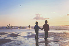 Silhouette of two kids, watching surfers on the beach Royalty Free Stock Photos
