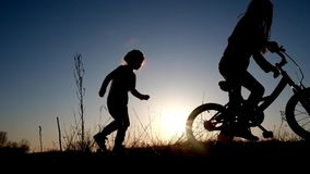 Silhouette of two little girls who play with bicycle. At meadow during sunset stock video footage