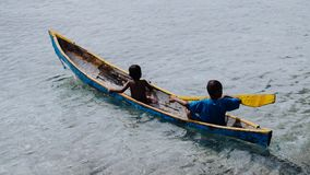 Silhouette of two local boys in a boat on Arborek Island in Raja Ampat, West Papua, Indonesia, near the famous Manta. Point dive spot Stock Photo