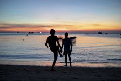 Silhouette of two man playing football on sea beach against suns Stock Image