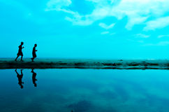 Silhouette of two man running at the beach Royalty Free Stock Photo