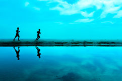 Silhouette of two man running at the beach Stock Image