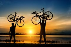 Silhouette two man stand in action lifting bicycle royalty free stock image