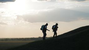 The silhouette of two man on the top of mountain with backpacks and other gear expressing energy and happiness. Two stock video