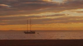 Silhouette two-masted yacht at the beautiful sunset on the sea. Mallorca island, Spain stock video