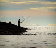 Silhouette of two men fishing. With boats and horizon in the distance royalty free stock photo