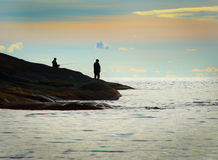 Silhouette of two men fishing. By the sea with horizon royalty free stock image