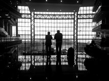 Silhouette of two men in a huge window. Black and white Stock Photo