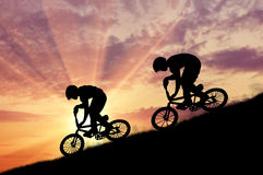 Silhouette of two moving cyclists Stock Photos