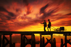 Silhouette of two people on the bridge at dusk. Stock Photos