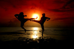 Silhouette of two people fighting. Silhouette of two people who are fighting photographed before sunrise Stock Image