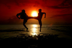 Silhouette of two people fighting. Silhouette of two people who are fighting photographed before sunrise Stock Photos