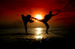 Silhouette of two people fighting. Silhouette of two people who are fighting photographed before sunrise Stock Photo