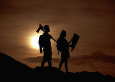 Silhouette of two people hiking and carrying camera and a map in nature at sunset Stock Photos
