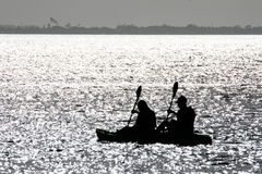 Silhouette Of Two People Rowing Stock Image