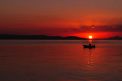 Silhouette of two people on the sea. Silhouette of two people in the boat on the sea at sunset. Podgora, Croatia Stock Photo