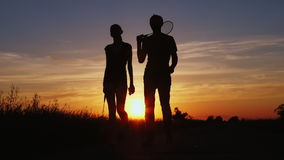 Silhouette of two people with tennis rackets in hands. A man and a woman are walking along the road against the sunset. Slow motion stock video footage