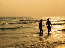 Silhouette of two people walking on beach. At sunset Royalty Free Stock Image