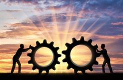 Business team concept. Silhouette of two people who want to connect the two gears in a single mechanism. Business team concept Royalty Free Stock Photos