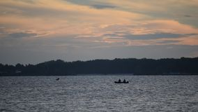 Silhouette of two persons in motor boat. At dawn on river or lake, probably fishermen stock footage