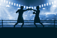 Silhouette of two professional asian boxer fight in the boxing m. Atch against stadium spotlight Royalty Free Stock Image