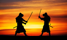 Silhouette of two samurais in duel. Picture with two samurais and sunset sky Royalty Free Stock Photography