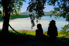 Silhouette two sister sit and relax with reservoir view Royalty Free Stock Photos