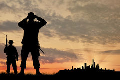 Silhouette of two soldiers with guns Royalty Free Stock Images