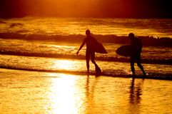 Silhouette of two surfer at yellow sunset Stock Images