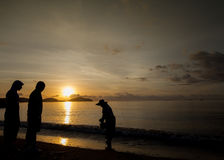 Silhouette of two tourists looking at fisherman searching for shells on the beach during sunrise in Phuket Royalty Free Stock Photos