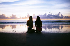 Silhouette of Two Woman Sitting Near Body of Water during Sunset Stock Photo