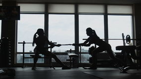 Silhouette of two womans pulling a rope in a sport fitness gym stock video footage