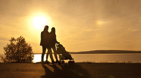 Silhouette of two women. Walking with a perambulator Royalty Free Stock Images