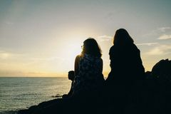 Silhouette of Two Women Facing Body of Water stock photography