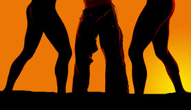 Silhouette of two womens legs and cowboys legs in the sunset Stock Photos
