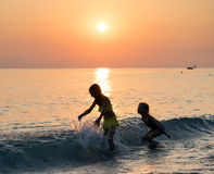 Silhouette of two young girl jumping in sea Royalty Free Stock Image