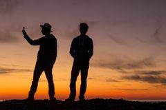 The silhouette of two young men taking photos during a beautiful sunset. royalty free stock photos