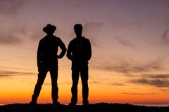 The silhouette of two young men turning back to a beautiful sunset. royalty free stock photo