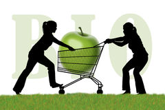 Women fighting for a shopping caddy with a bio apple. Silhouette of two young women trying to monopolize a shopping caddy with a huge green bio apple Stock Photo