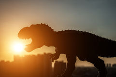 Silhouette of tyrannosaurus and buildings in a sunset time Royalty Free Stock Images