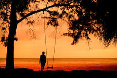 Silhouette of unidentified girl on beach with sunset light Stock Photography