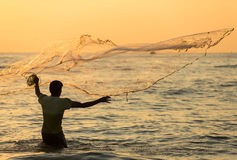 Silhouette of the unidentified Indian fisherman throwing net in sea. On sunset in Fort Kochi, India royalty free stock image