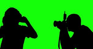Unknown man photographing a female model. Silhouette of unknown man photographing a female model in the studio, shot in 4k resolution with green screen stock footage