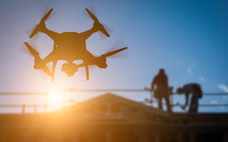 Silhouette of Unmanned Aircraft System UAV Quadcopter Drone In. The Air Over Building Under Construction royalty free stock image