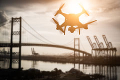 Silhouette of Unmanned Aircraft System UAV Quadcopter Drone In. The Air Over Shipping Port Stock Photos