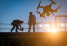 Silhouette of Unmanned Aircraft System UAV Quadcopter Drone In. The Air Over Building Under Construction stock photo