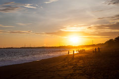Silhouette of unrecognizable tourists and local people with father and son taking selfie at Boracay beach during sunset - Exclusiv stock photo