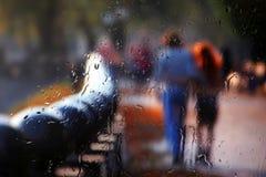 Silhouette vague de deux personnes par le verre pluvieux Photographie stock