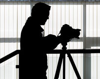 Silhouette of video and photographic equipment. On a tripod at the workplace indoors. Photographer in the background Royalty Free Stock Photography